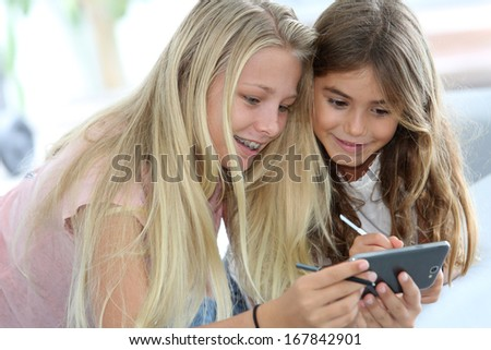 Young girls playing together with smartphone - stock photo