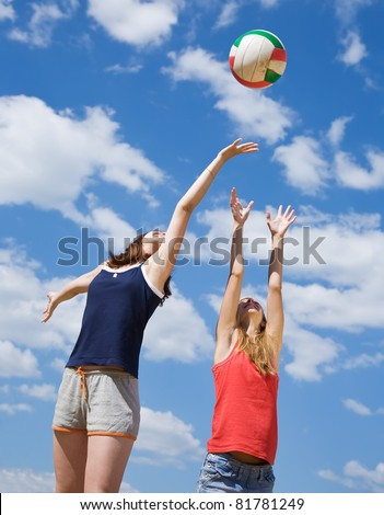 Young girls playing volleyball in the beach