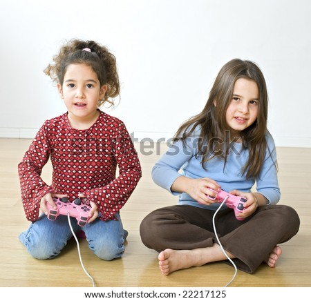young  girls playing with playstation together - stock photo