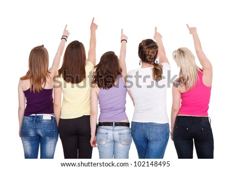 Young girls pointing in copy space and looking up, back view - stock photo