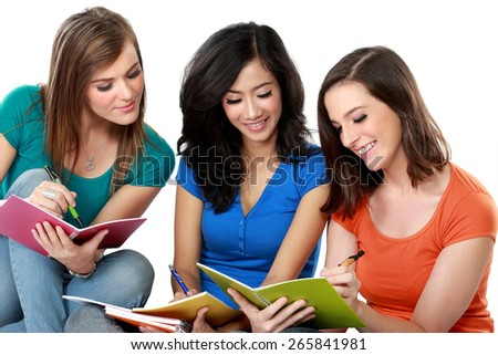 Young girls reading her book sitting on the floor together - stock photo