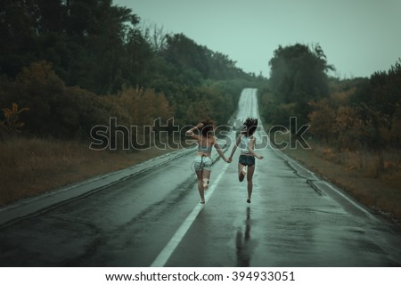 Young girls runing on the road in the rain - stock photo