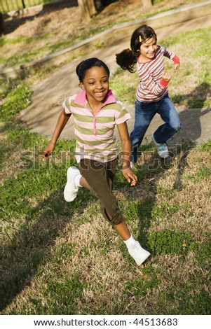 Young girls running on grass. Vertically framed shot. - stock photo