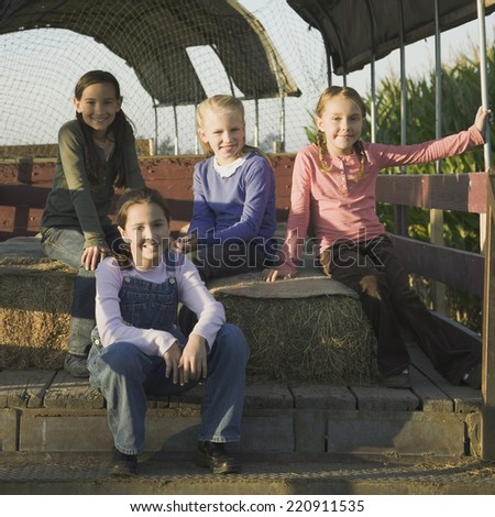 Young girls sitting on hay bales in back of truck - stock photo
