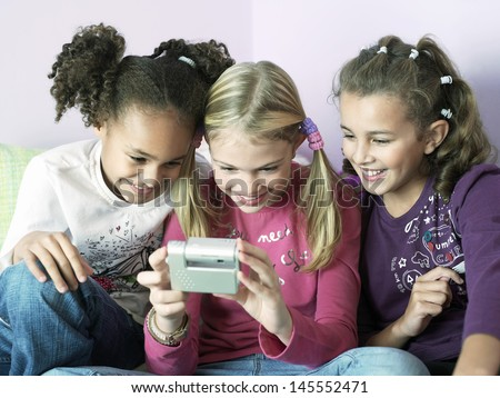 Young girls sitting side by side and playing with electrical gadget - stock photo