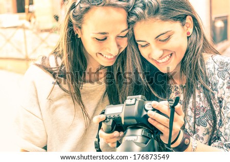 Young girls watching photos in a digital Camera