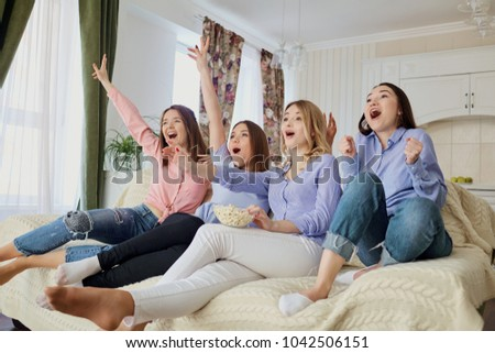 Young girls watching TV, eating popcorn sitting on the couch.