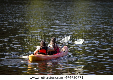 Young girls with oars rowing in the bright kayak on Trillium Lake reflection of the sparkling green of surrounding lake and forest patches of sunlight in shallow water ripples - great way to relax