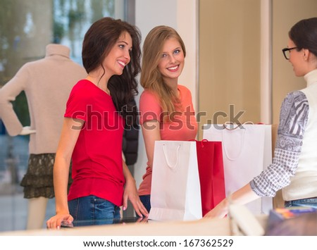 Young girls with shopping bags in store standing in front of cash - stock photo