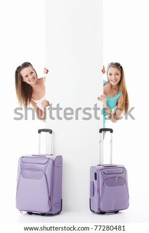 Young girls with suitcases and empty billboard on a white background - stock photo