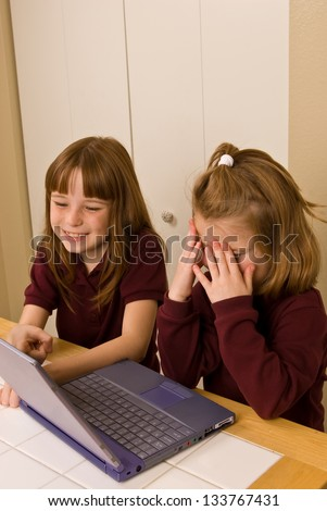 Young girls working on a laptop computer - One young girl covers her face in  as the other girl smiles and points out, what appears to be a mistake, on the screen - stock photo