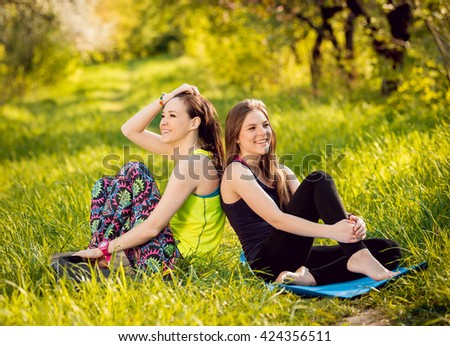 Young girls yoga in the park. Relax in nature