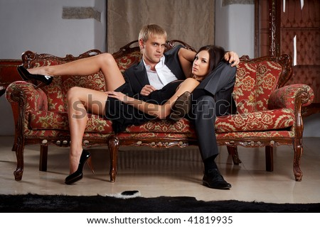 Young glamorous passionate couple sitting on a sofa - stock photo