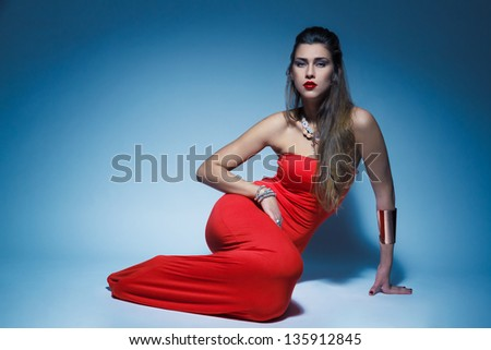 Young glamour woman in red dress long hair in studio