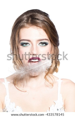 Young glamour woman with bright makeup on pretty face and feather in purple lips on light background closeup