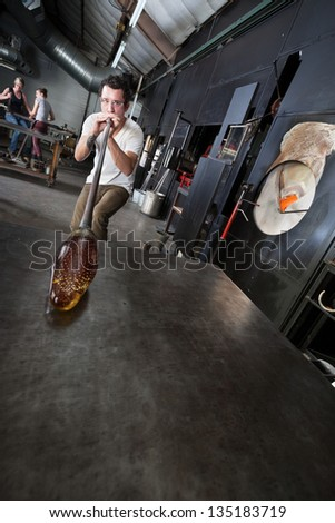 Young glass artisans creating vases in industrial arts school - stock photo