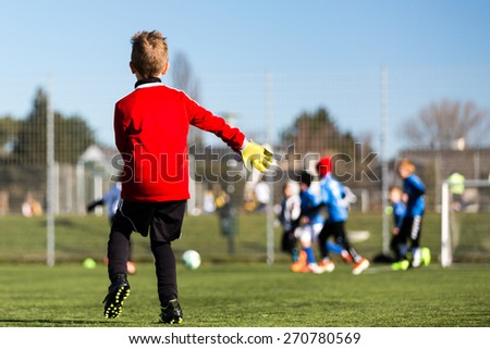 Young goal keeper and his youth team during a kids soccer match outdoors on green soccer pitch. - stock photo