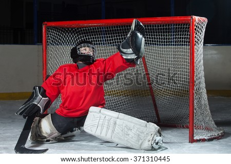 Young goalkeeper catching a flying puck - stock photo