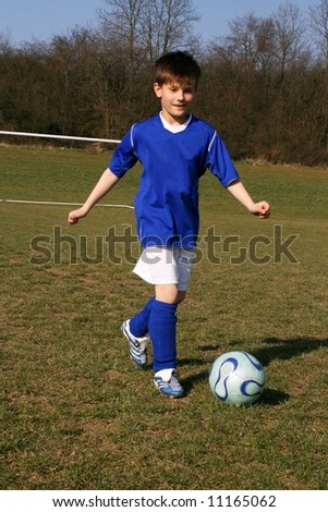 Young goalkeeper quickly catches ball - stock photo