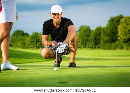 Young golf player on course putting, he aiming for his put shot - stock photo