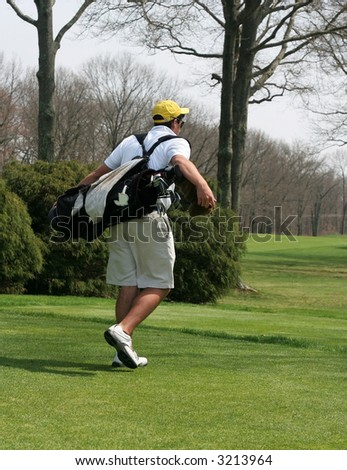 young golfer carrying clubs - stock photo