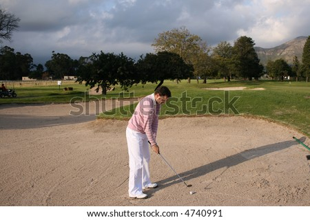 Young golfer concentrating on a shot before hitting the ball from the bunker - stock photo