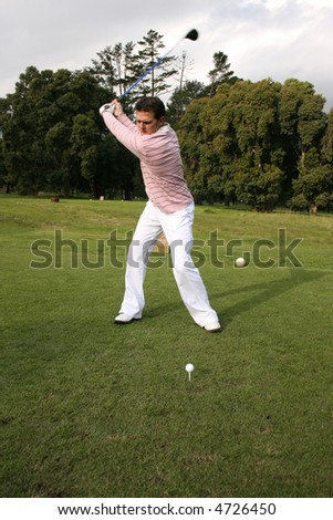 Young golfer during a shot with his driver - stock photo