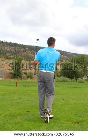 Young golfer following his shot on the fairway