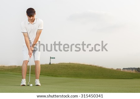 Young golfer getting ready to hit the ball - stock photo