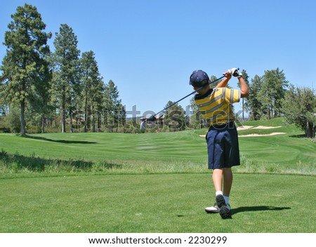 Young golfer hitting a nice tee shot - stock photo