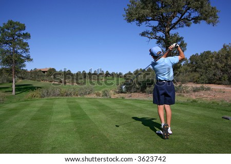 Young golfer hitting a nice tee shot with ball clearly visible - stock photo