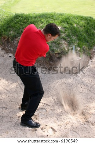 Young golfer hitting a shot out of a bunker - stock photo
