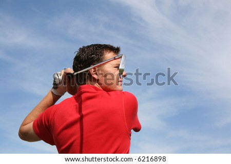 Young golfer hitting an iron against a half cloudy sky