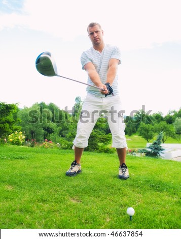 Young golfer holding club ready to strike ball on golf course.