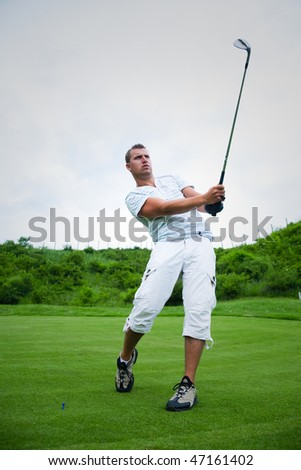 Young golfer in swing pose after striking ball.