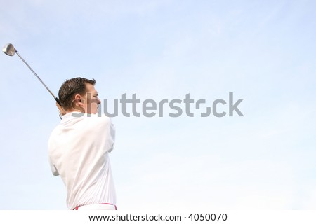 Young golfer in white against a pale blue sky - stock photo