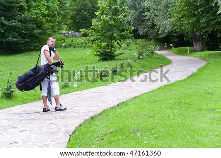 Young golfer on stone walkway carrying bag with clubs.