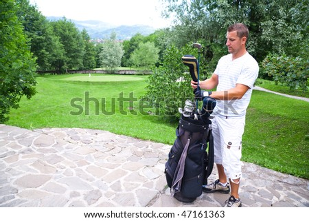 Young golfer on stone walkway taking out clubs from bag.