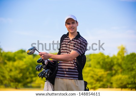 Young Golfer Ready to Swing Club Early Morning  under Summer Blue Sky - stock photo
