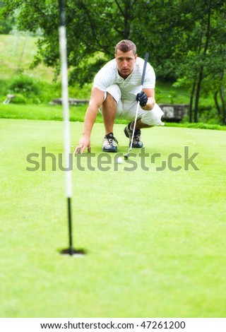 Young golfer squatting to check distance to the hole.