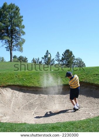 Young golfer successfully hitting golf ball out of a sand trap - stock photo