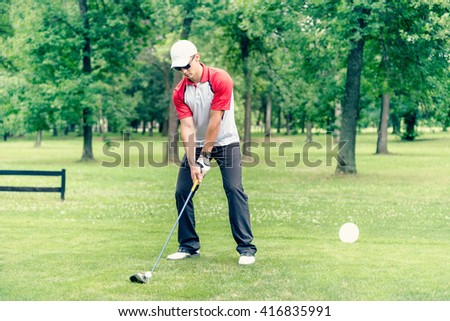 Young golfer teeing off