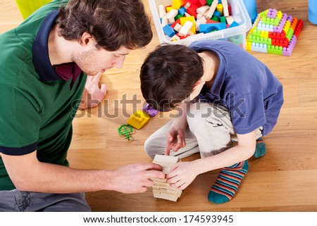 Young good daddy playing toys with his son at home - stock photo