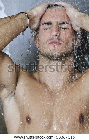young good looking and attractive man with muscular body wet taking shower in bath with black tiles in background - stock photo