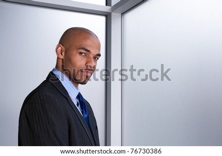 Young good-looking businessman beside an office window.