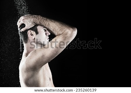 Young good looking man taking shower in bath