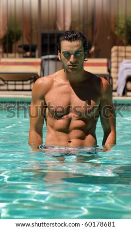 young good looking muscular man in pool - stock photo