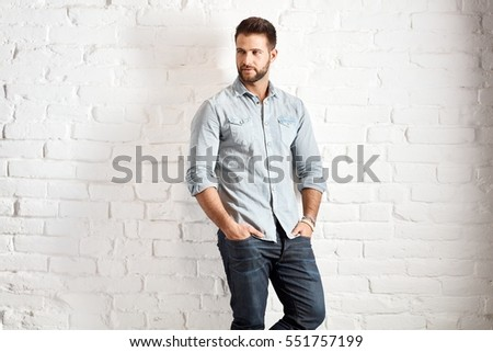 Young goodlooking caucasian man in casual outfit standing at white brick wall, plenty of copyspace.