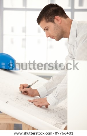 Young goodlooking engineer making plans on drawing table.? - stock photo