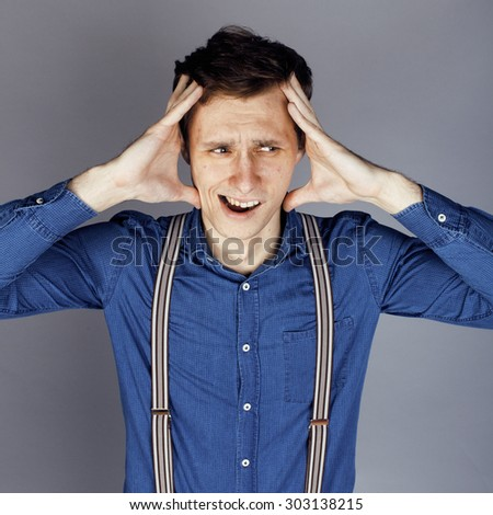 young goofy man with pimples pointing in studio, stupid bookwarm little crazy - stock photo